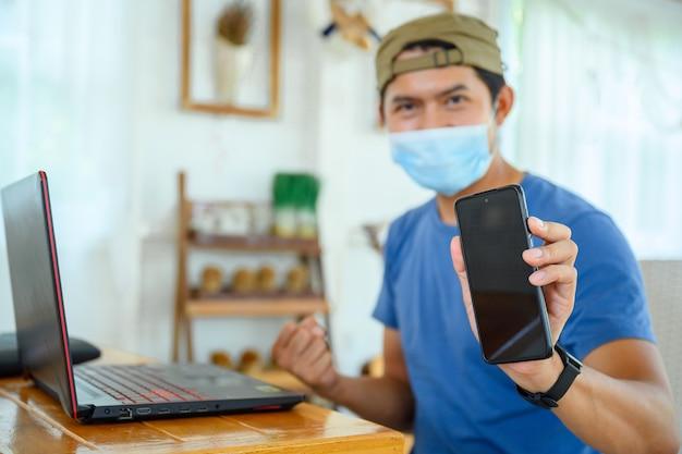 Jovem usando uma máscara trabalhar online com sucesso mostrar telefone celular com tela em branco homem asiático trabalhando em casa