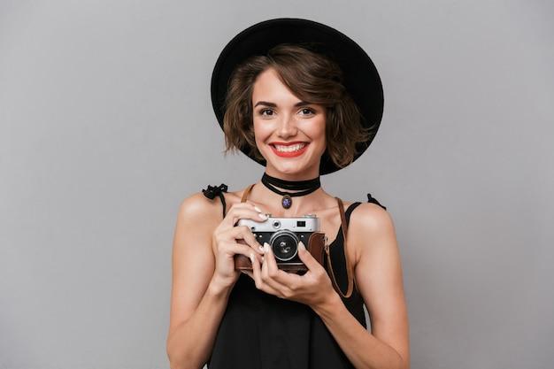 Jovem usando vestido preto e chapéu fotografando na câmera retro, isolada sobre uma parede cinza