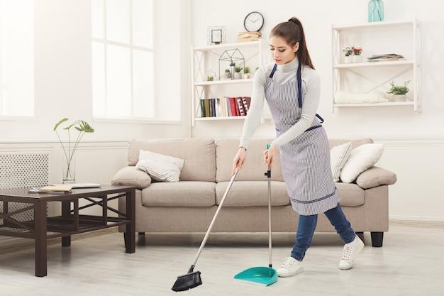Jovem varrendo a casa com vassoura e pá