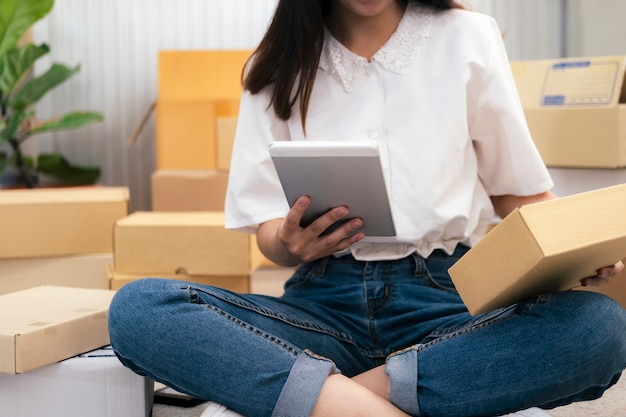 Jovem vendedor online que verifica a ordem do cliente e prepara a entrega da caixa de encomendas aos clientes
