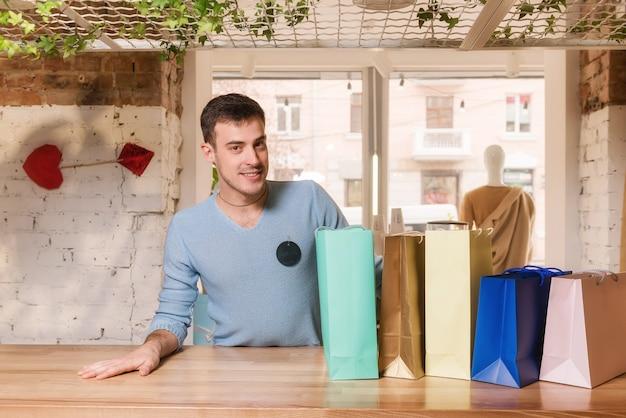 Jovem vendedor sorridente com sacolas de compras na loja de roupas
