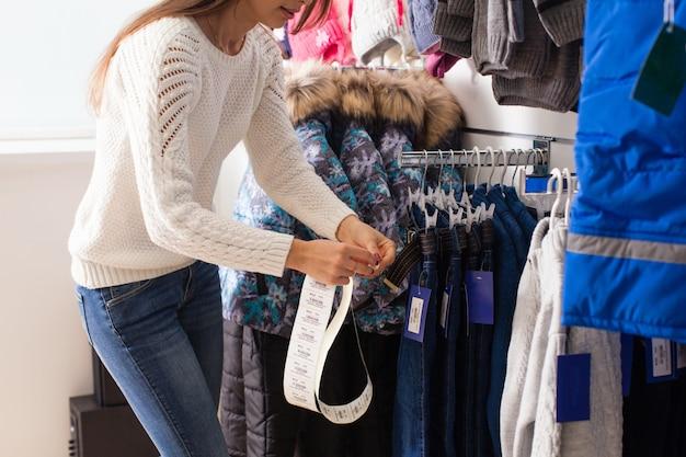 Jovem vendedora cola os preços das mercadorias - roupas infantis