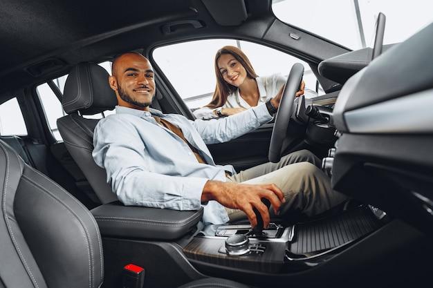Jovem vendedora em showroom de carros mostrando um carro para seu cliente