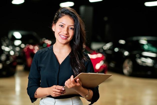 Jovem vendedora latina vendendo carros de luxo