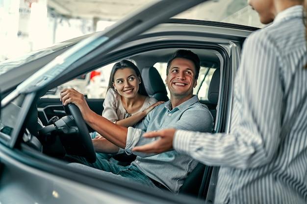 Jovem vendedora mostra um casal apaixonado um carro em uma concessionária de automóveis. comprar ou alugar um carro.