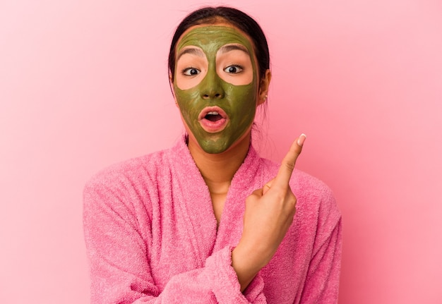Jovem venezuelana de roupão e máscara facial isolada em um fundo rosa apontando para o lado