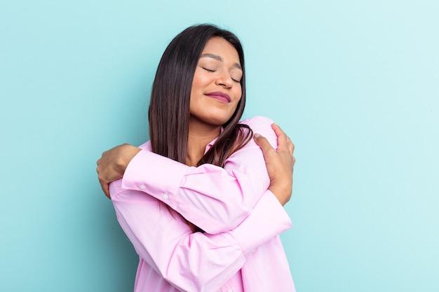Jovem venezuelana isolada em um fundo azul abraços, sorrindo despreocupada e feliz.