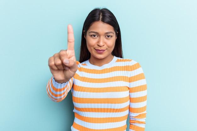 Jovem venezuelana isolada em um fundo azul, mostrando o número um com o dedo.