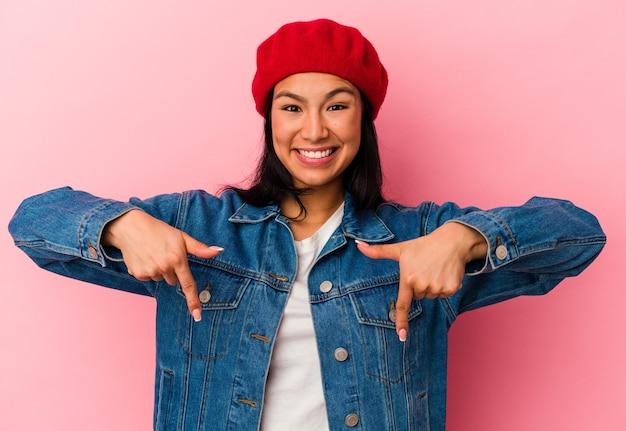 Jovem venezuelana isolada em um fundo rosa aponta para baixo com os dedos, sentimento positivo.