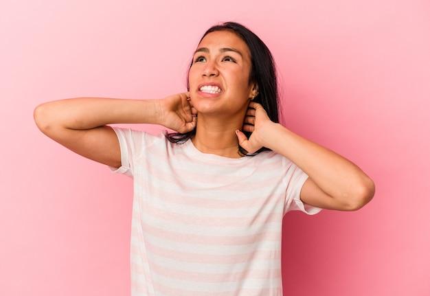 Jovem venezuelana isolada em um fundo rosa, sofrendo de dores no pescoço devido ao estilo de vida sedentário.