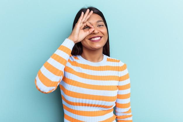 Jovem venezuelana isolada sobre fundo azul animada mantendo o gesto ok no olho.