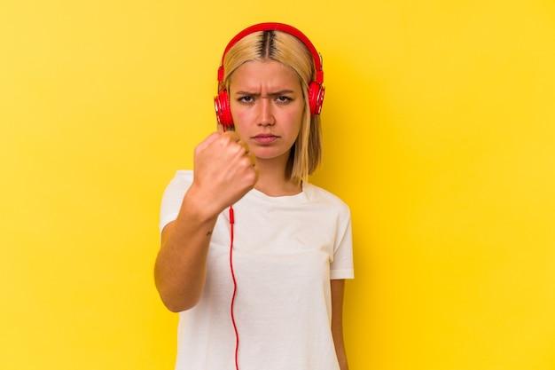Jovem venezuelana ouvindo música isolada em fundo amarelo, mostrando o punho para a câmera, expressão facial agressiva.