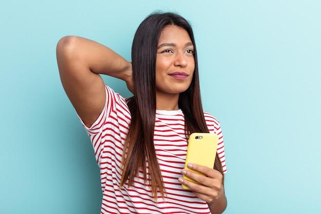 Jovem venezuelana segurando o telefone celular isolado em um fundo azul, tocando a parte de trás da cabeça, pensando e fazendo uma escolha.