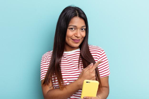 Jovem venezuelana segurando telefone celular isolado em um fundo azul, sorrindo e apontando de lado, mostrando algo no espaço em branco.