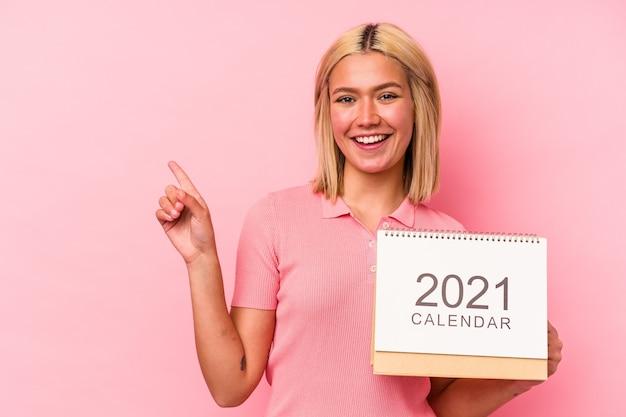 Jovem venezuelana segurando um calendário 2021 isolado na parede rosa, sorrindo e apontando para o lado, mostrando algo no espaço em branco.