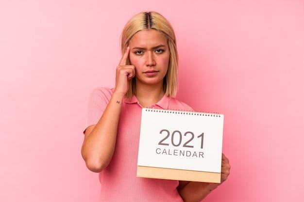 Jovem venezuelana segurando um calendário isolado no fundo rosa, apontando o templo com o dedo, pensando, focado em uma tarefa.