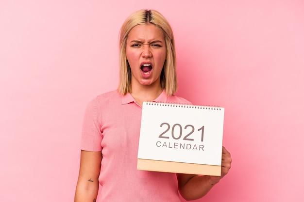 Jovem venezuelana segurando um calendário isolado no fundo rosa, gritando com muita raiva e agressividade.
