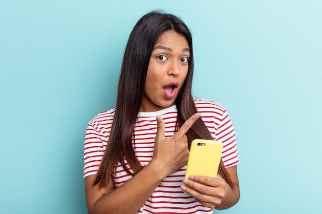 Jovem venezuelana segurando um celular isolado em um fundo azul apontando para o lado