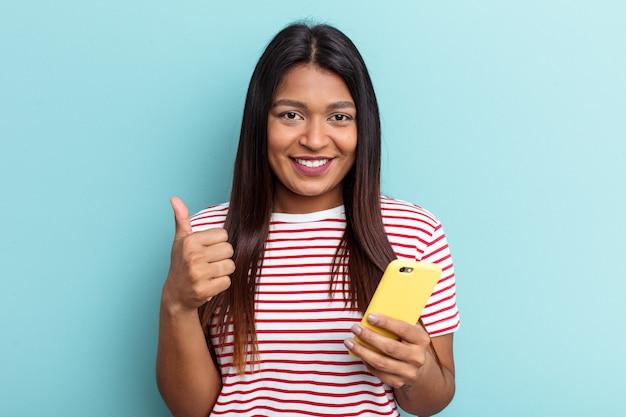Jovem venezuelana segurando um celular isolado em um fundo azul, sorrindo e levantando o polegar