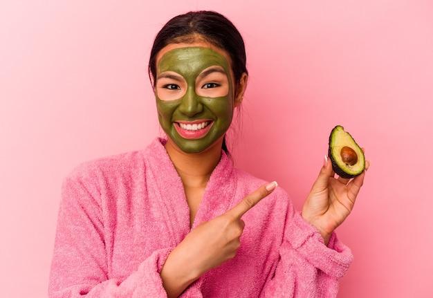 Jovem venezuelana usando máscara facial isolada em fundo rosa
