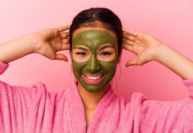 Jovem venezuelana vestindo roupão de banho e máscara facial isolada em fundo rosa