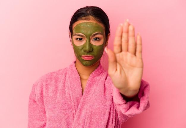 Jovem venezuelana vestindo um roupão de banho e máscara facial isolada em um fundo rosa em pé com a mão estendida, mostrando o sinal de pare, impedindo você.