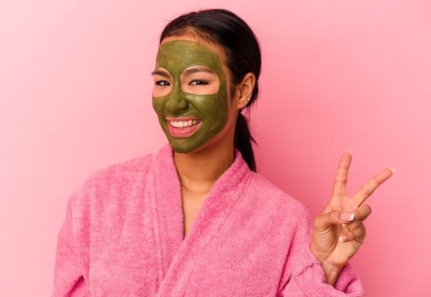 Jovem venezuelana vestindo um roupão de banho e máscara facial isolada no fundo rosa alegre e despreocupada, mostrando um símbolo da paz com os dedos.