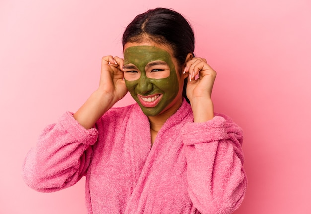 Jovem venezuelana vestindo um roupão de banho e máscara facial isolada no fundo rosa, cobrindo as orelhas com as mãos.