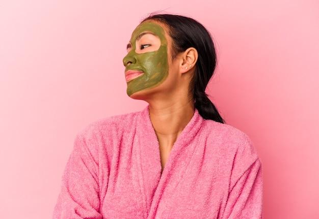 Jovem venezuelana vestindo um roupão de banho e máscara facial isolada no fundo rosa, olhando de soslaio com expressão duvidosa e cética.