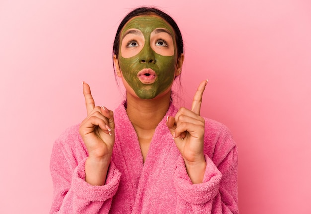 Jovem venezuelana vestindo um roupão de banho e uma máscara facial isolada em um fundo rosa apontando de cabeça para baixo com a boca aberta.