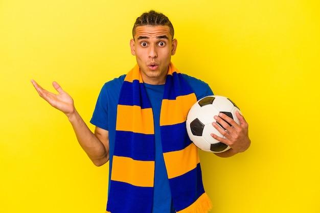 Jovem venezuelano assistindo futebol isolado em fundo amarelo surpreso e chocado.