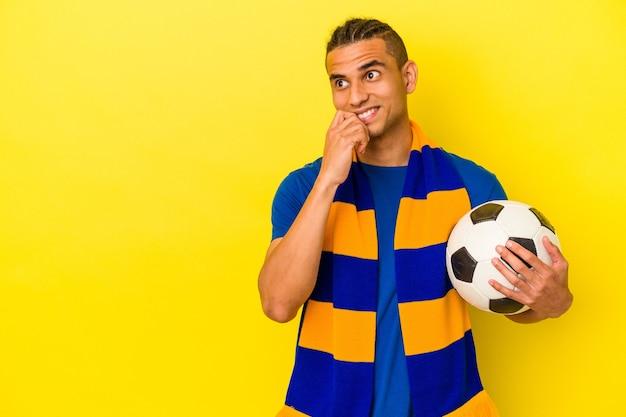 Jovem venezuelano assistindo futebol isolado em um fundo amarelo relaxado pensando em algo olhando para um espaço de cópia.