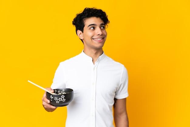 Jovem venezuelano isolado em amarelo olhando para cima enquanto sorri enquanto segura uma tigela de macarrão com pauzinhos