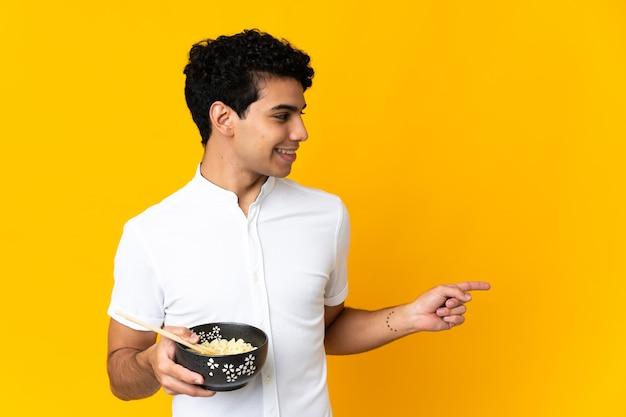 Jovem venezuelano isolado em fundo amarelo apontando para o lado para apresentar um produto, segurando uma tigela de macarrão com pauzinhos