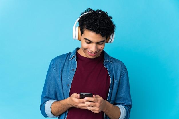 Jovem venezuelano isolado em um fundo azul ouvindo música e olhando para o celular