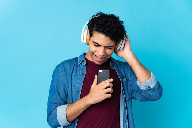 Jovem venezuelano isolado no azul ouvindo música com um celular e cantando