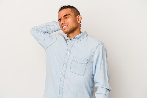 Jovem venezuelano isolado no fundo branco, sofrendo de dores no pescoço devido ao estilo de vida sedentário.