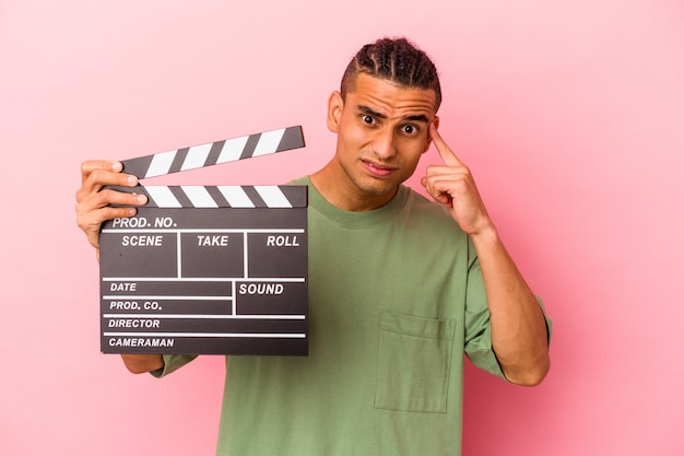 Jovem venezuelano segurando uma claquete isolada no fundo rosa, mostrando um gesto de decepção com o dedo indicador.