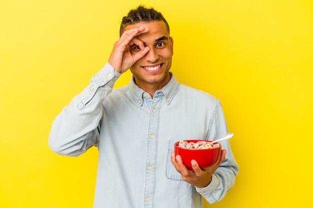 Jovem venezuelano segurando uma tigela de cereais isolada em fundo amarelo