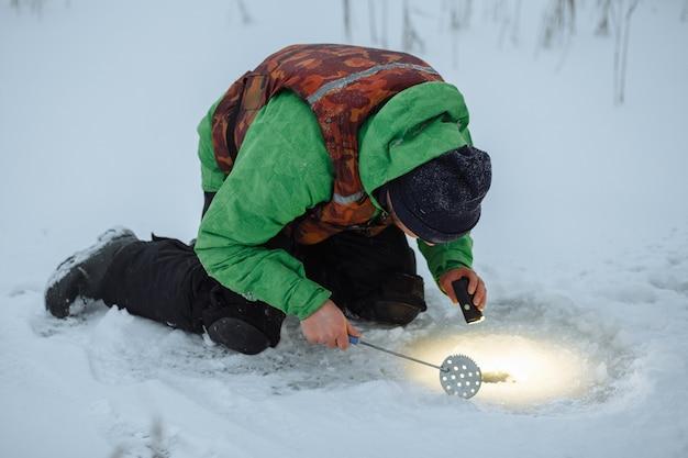 Jovem verifica um buraco em um lago congelado em um pescador de inverno