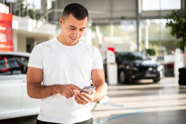 Jovem, verificando seu telefone na concessionária