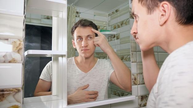 Jovem, verificando sua pele no banheiro.