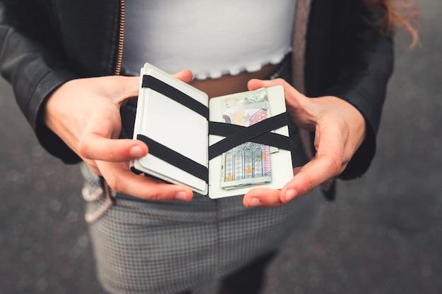 Jovem verificando uma carteira com euros e cartões