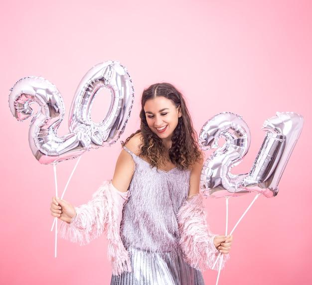 Jovem vestida festivamente e fofa sorrindo em uma parede rosa com balões prateados para o conceito de ano novo