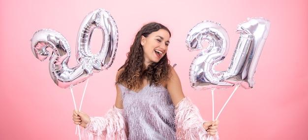Jovem vestida festivamente rindo em um fundo rosa com balões de natal prateados para o conceito de ano novo