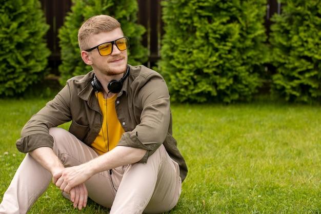 Jovem vestido casualmente com óculos amarelos sentado na grama verde com fones de ouvido no pescoço, olhando para longe no espaço verde da cópia do pano de fundo