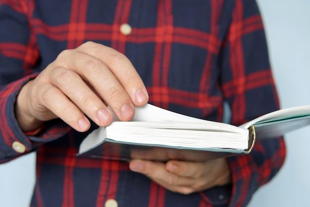 Jovem vestido casualmente, segurando um livro aberto folheando as páginas. livro de estudos para jovens alunos. a pessoa adora ler. homem folheia a página. procurando informações de fonte confiável.