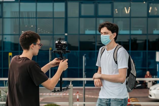 Jovem vestido com camiseta preta, calça jeans, tênis vermelho e óculos filmando outro homem vestido com camiseta branca, shorts jeans, calçado preto, mochila e máscara cirúrgica em frente ao aeroporto