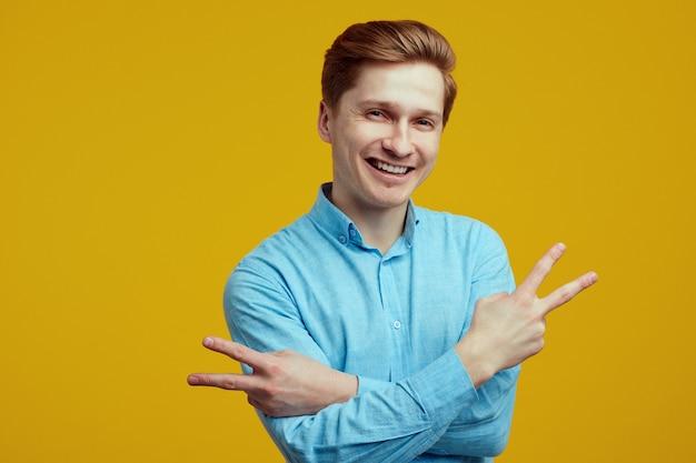 Jovem vestido com uma camisa azul mostrando um gesto de paz com as mãos cruzadas