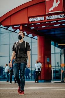 Jovem vestido de camiseta preta, calça jeans, tênis vermelho, mochila, máscara cirúrgica e óculos andando longe do aeroporto